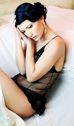 Bewitching Ukrainian girl sitting pretty on the bed