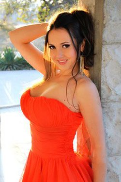 Sultry Ukrainian attorney in a red tube dress leaning on the wall