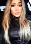 Brazilian girl wearing a leather jacket inside a car