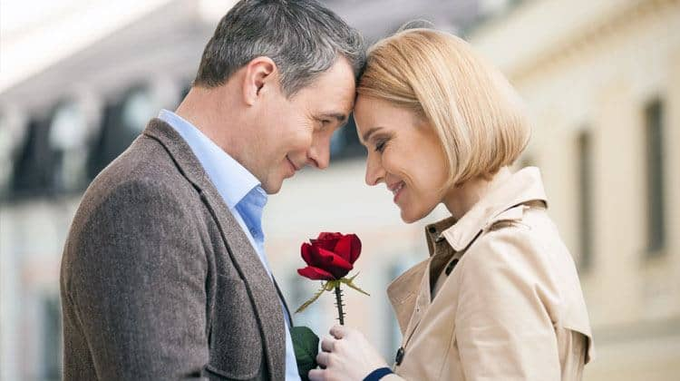 an older man giving a rose to his date