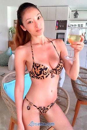 hot Thai babe holding a glass of wine