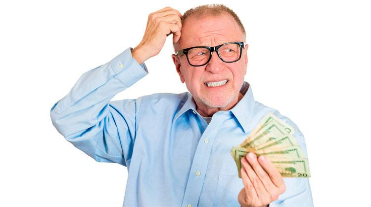 worried old man holding money