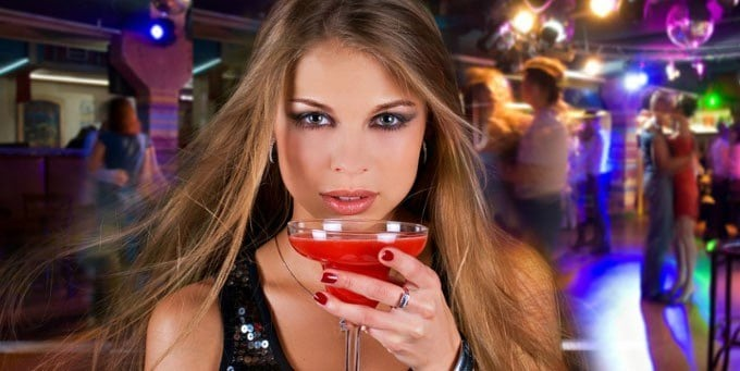 young woman at the bar drinking cocktail