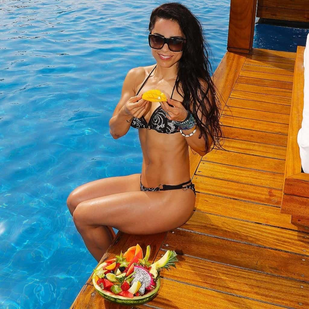 Andreia Brazier eating fruit by the pool