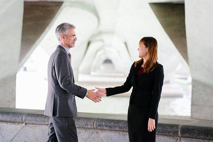 young woman and old guy having a handshake