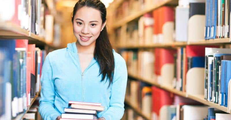 educated Chinese girl holding books in the library