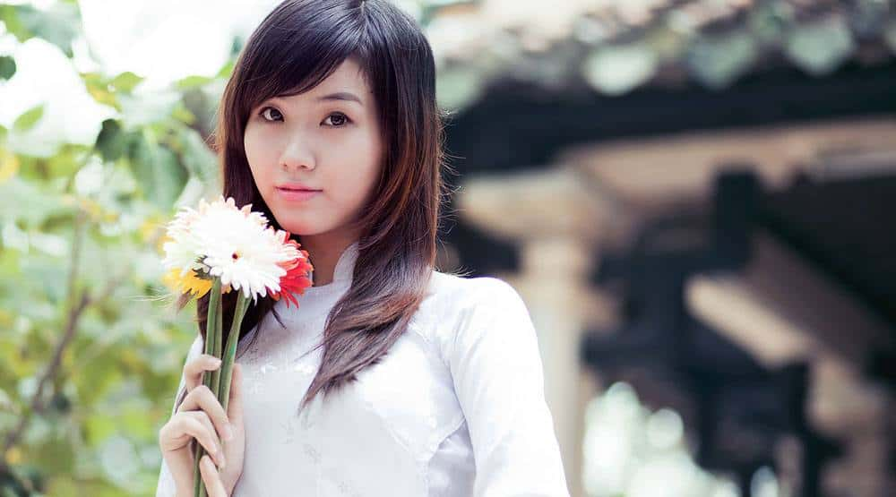 lovely Vietnamese babe holding beautiful flowers