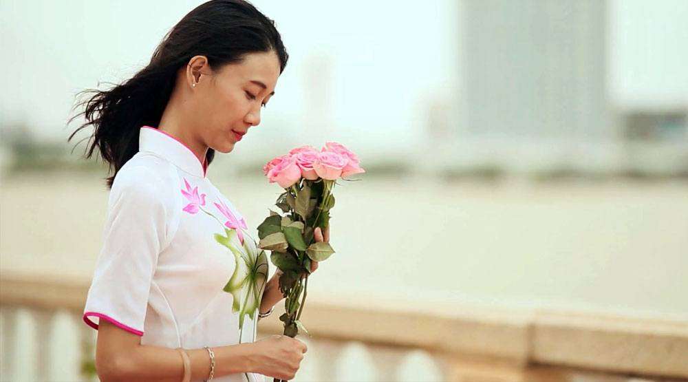 Vietnamese girl wearing a traditional dress holding flowers