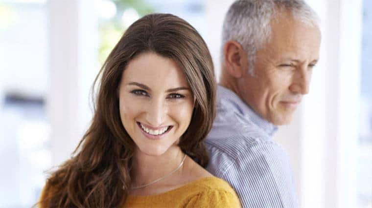 beautiful girl smiling with an older man at her back