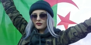 Cute Algerian woman holding a flag