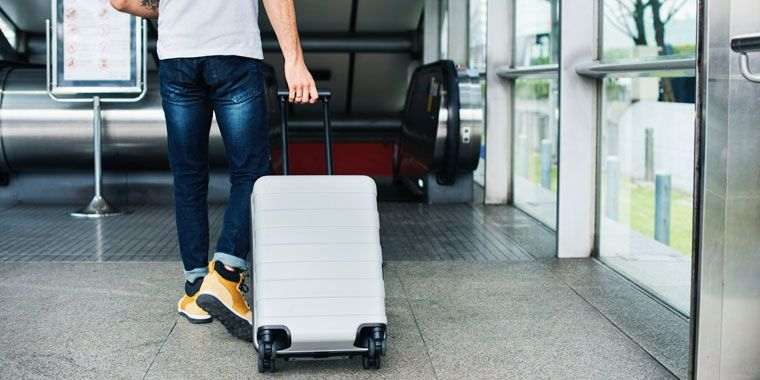 man holding a rolling luggage