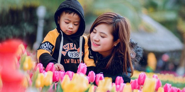 mom and child in front of flowers