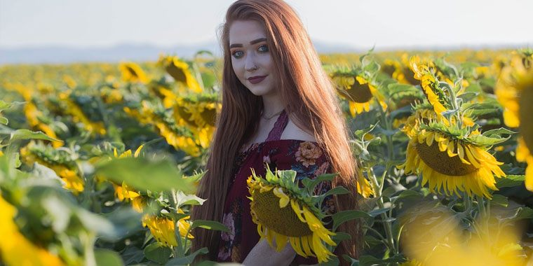 pretty redhead in the middle of the sunflower field