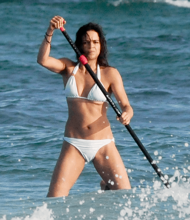 Michelle Rodriguez paddling at the beach