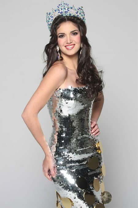 Adriana Vasini in a shiny silver dress with a crown