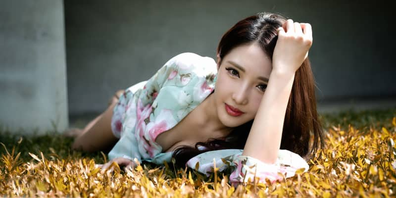 Chinese woman having a pictorial on the grass