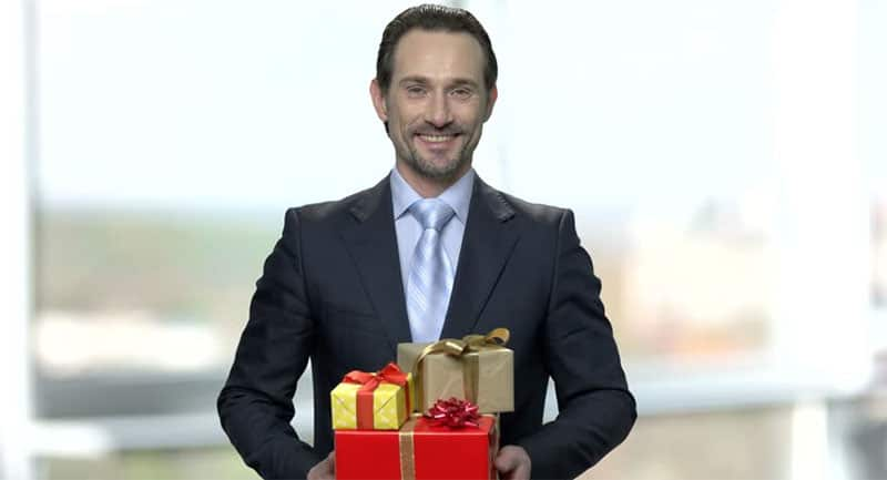 middle aged man holding gifts
