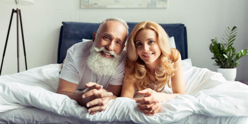 older guy and a young woman photographed on a bed