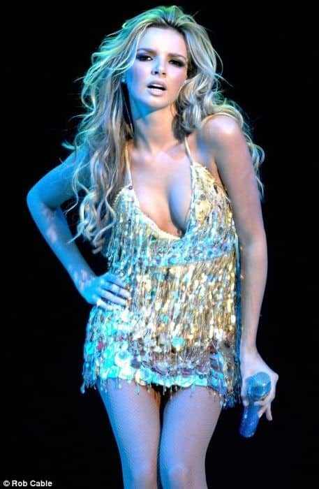 Nadine Coyle seductive on stage holding a mic