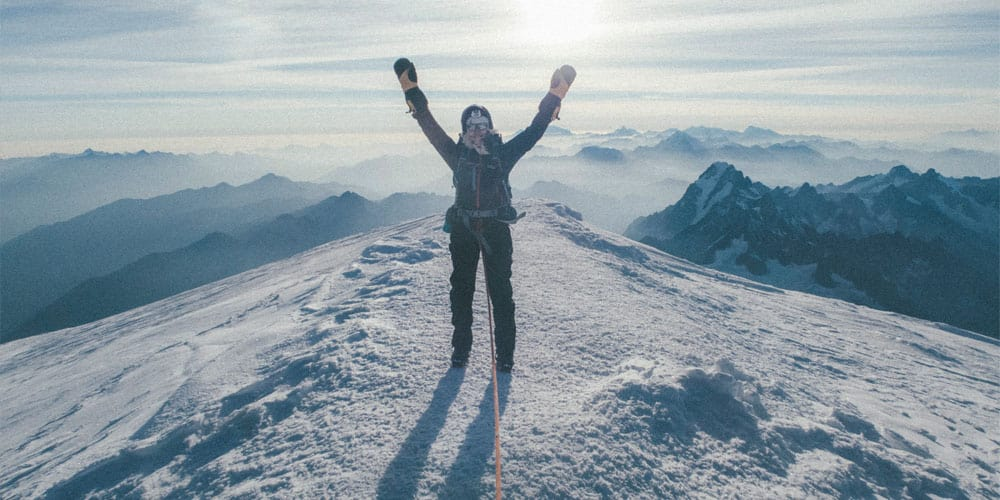 woman on top of a snowy mountain
