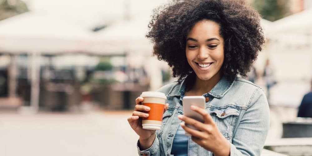 young Dominican girl holding coffee and smartphone
