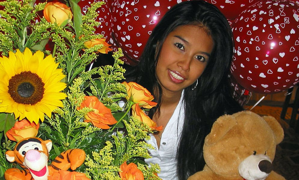 beautiful Colombian girl surrounded with gifts and flowers