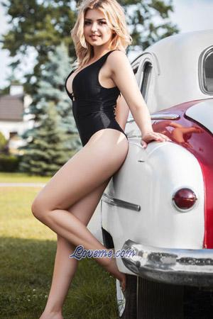 young Ukraine blonde beside car