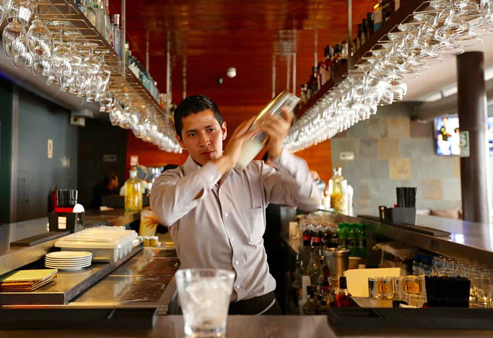 bartender in Lima, Peru mixing Pisco Sour drink