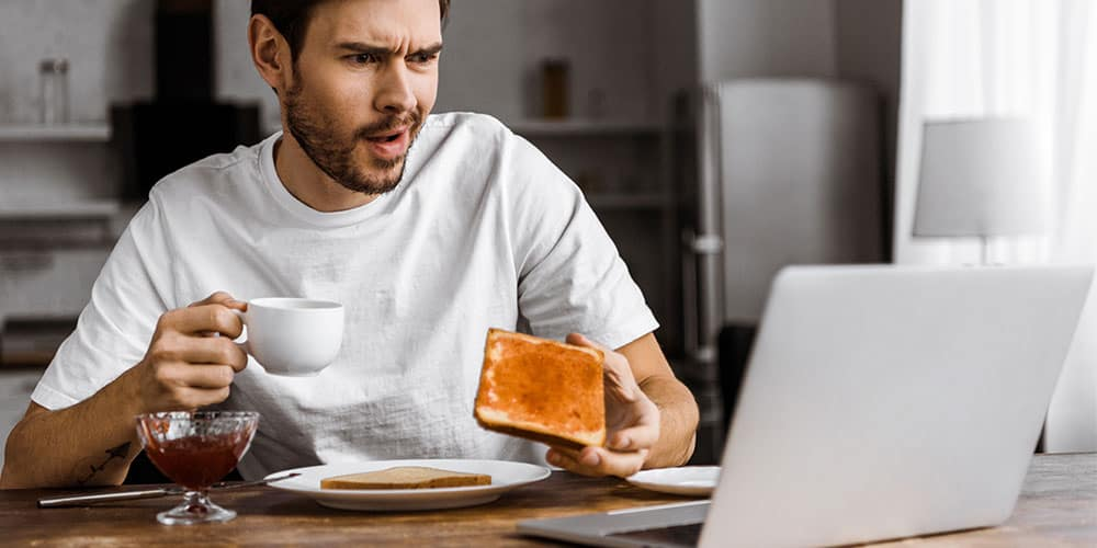 man eating breakfast in front of laptop